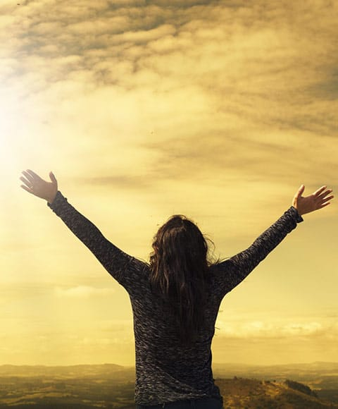 Femme libérée, levant les bras vers le ciel