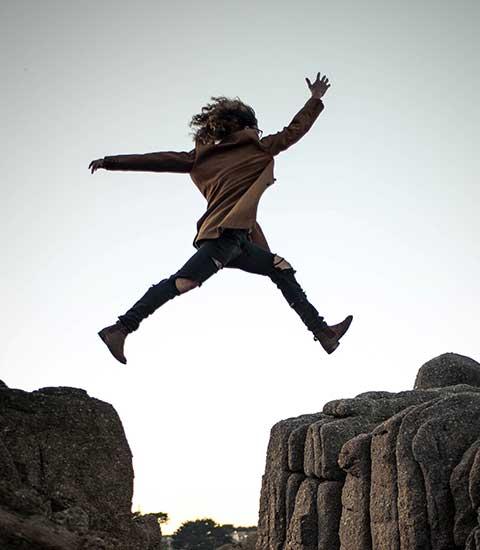 Femme sautant d'un rocher à l'autre