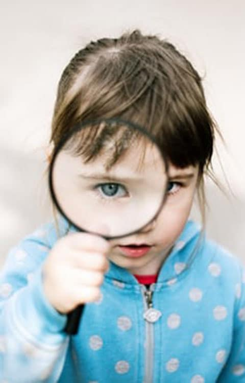 Petite fille observant au travers d'une loupe